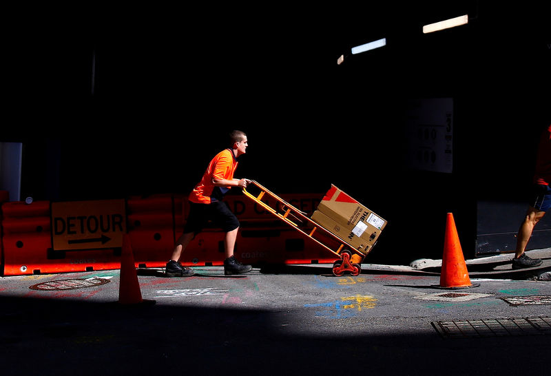 © Reuters. FILE PHOTO: A worker pushes a trolley loaded with goods past a construction site in the central business district of Sydney