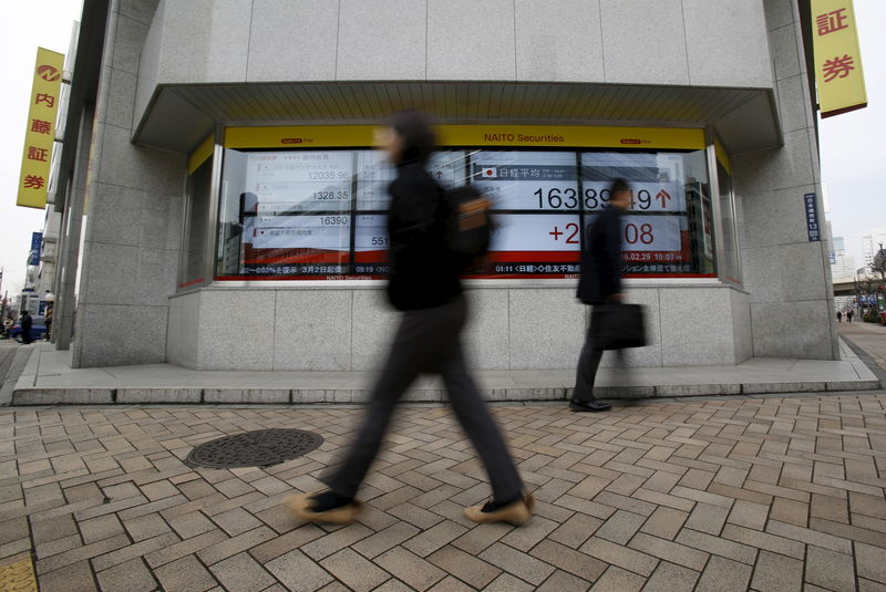 © Reuters. Pedestrians walk pass an electronic board outside a brokerage in Tokyo