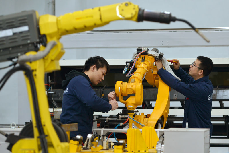 © Reuters. Men work on a production line that produces robot arm at the factory in Huzhou, Zhejiang