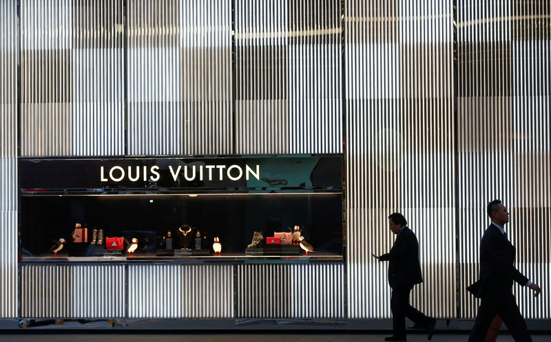 © Reuters. FILE PHOTO: Men walking past a boutique of Louis Vuitton luxury goods company in Beijing
