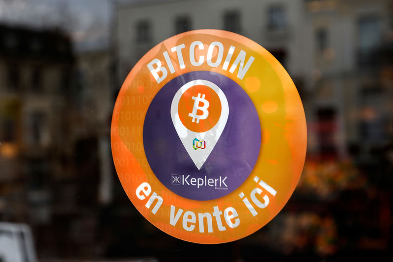 © Reuters. A sticker of French startup Keplerk, indicating that customers can buy bitcoins, is seen on a tobacco shop at Rueil-Malmaison