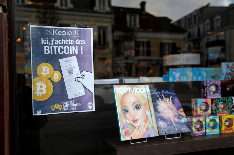 © Reuters. FILE PHOTO: A placard of French startup Keplerk, for clients to purhcase bitcoins, is seen inside a tobacco shop at Rueil-Malmaison