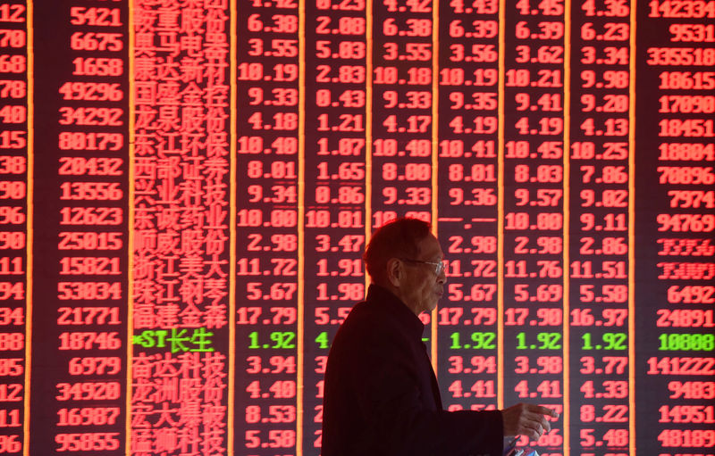 © Reuters. FILE PHOTO: The man is seen in front of an electronic board showing stock information on the first day of the Sour year trade at a brokerage house in Hangzhou