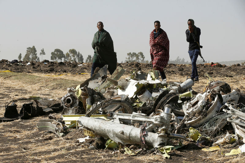 © Reuters. FILE PHOTO: Ethiopian police officers walk past the debris of the Ethiopian Airlines Flight ET 302 plane crash, near the town of Bishoftu, near Addis Ababa
