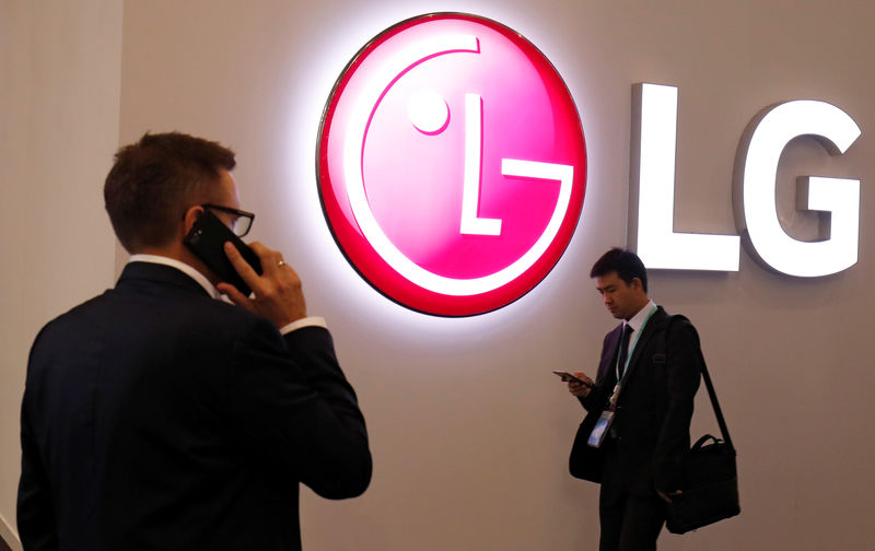 © Reuters. Visitors use their mobile phones next to LG booth during the Mobile World Congress in Barcelona