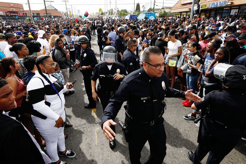 © Reuters. LAPD officers reopen a path for the funeral procession after fans filled the intersection while waiting for the procession following a memorial for rapper Nipsey Hussle in Los Angeles