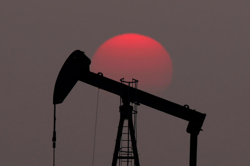 © Reuters. FILE PHOTO: The sun sets behind a pump-jack outside Saint-Fiacre