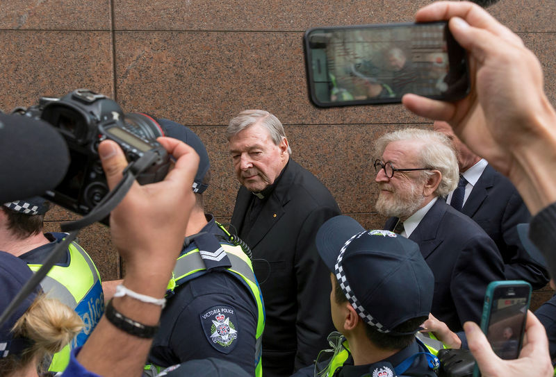 © Reuters. FILE PHOTO - Vatican Treasurer Cardinal George Pell is surrounded by Australian police and members of the media as he leaves the Melbourne Magistrates Court in Australia