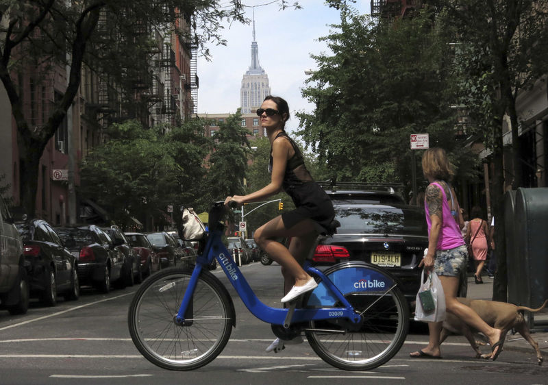 © Reuters. FILE PHOTO: The Empire State Building is seen in the distance as a woman rides a Citibike in the Soho neighbourhood of New York