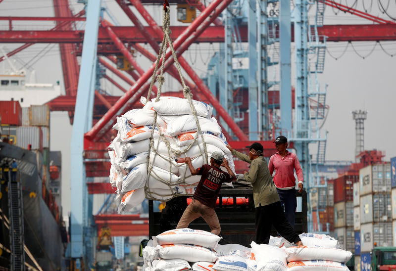© Reuters. FILE PHOTO: Workers help unload bags of rice from a cargo ship onto a truck at Tanjung Priok Port in Jakarta,