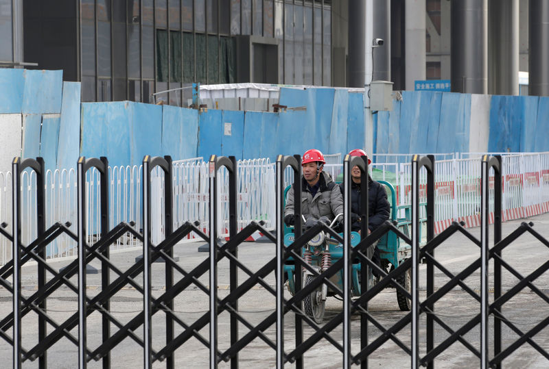 © Reuters. FILE PHOTO: Workers are seen at a construction site in Beijing's central business area