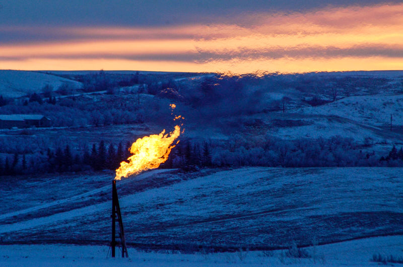 © Reuters. A natural gas flare on an oil well pad burns as the sun sets outside Watford City, North Dakota