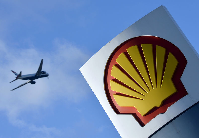 © Reuters. Passenger plane flies over a Shell logo at a petrol station in west London