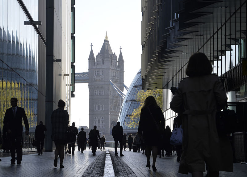 © Reuters. FILE PHOTO: City workers head to work during the morning rush hour in London
