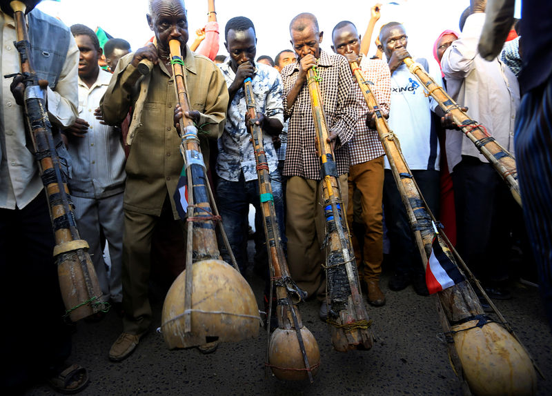 © Reuters. Sudanese demonstrators play traditional instruments during the sit-in protest outside Defence Ministry in Khartoum