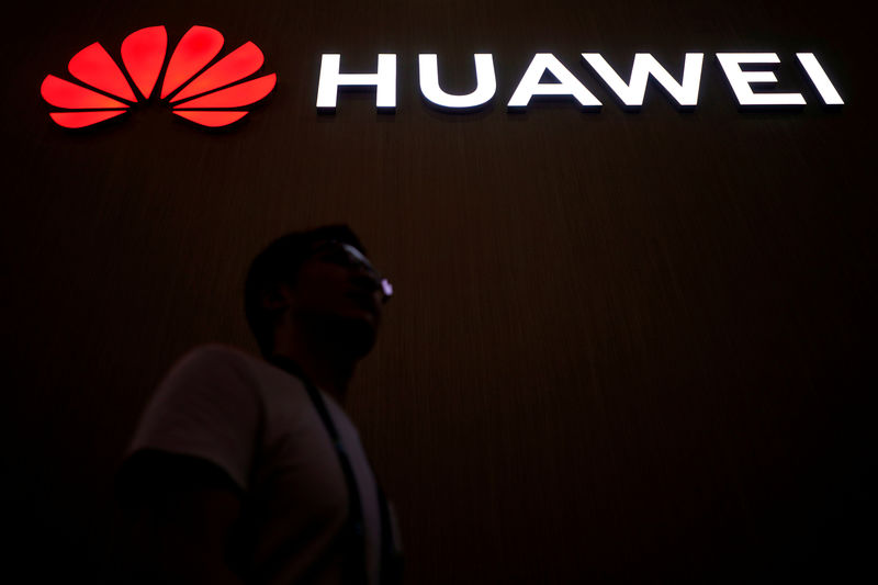 © Reuters. FILE PHOTO: A man walks past a sign board or Huawei at CES (Consumer Electronics Show) Asia 2018 in Shanghai