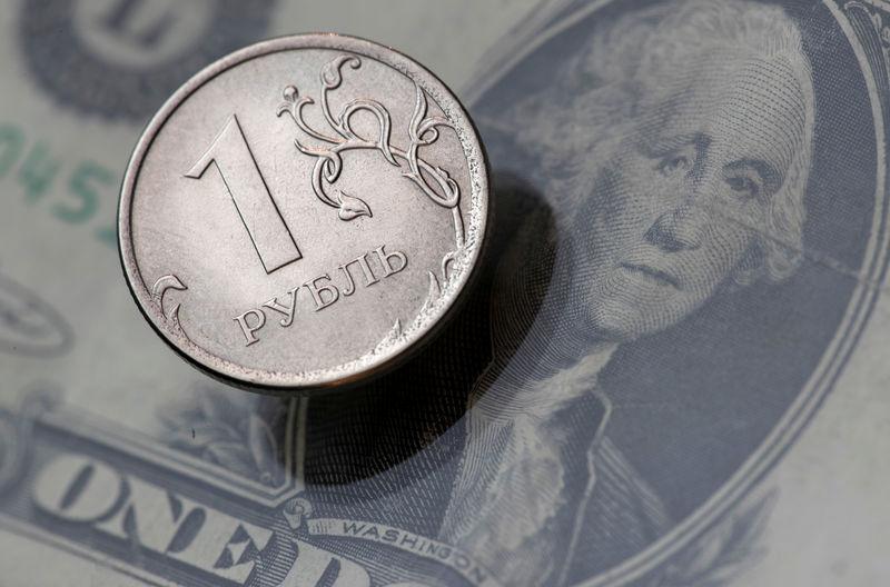 © Reuters. Рублевая монета и долларовая банкнота