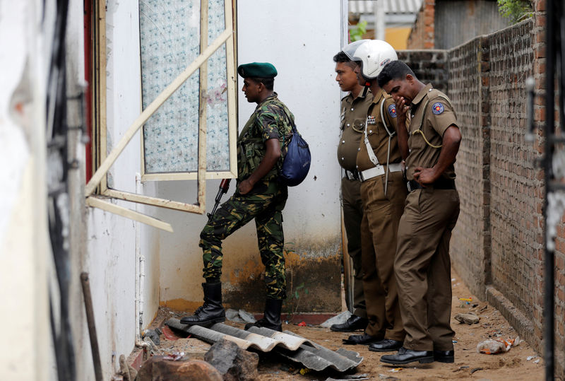 © Reuters. Security personnel at the site of an overnight gun battle, between troops and suspected Islamist militants, on the east coast ofSriLanka, in Kalmunai
