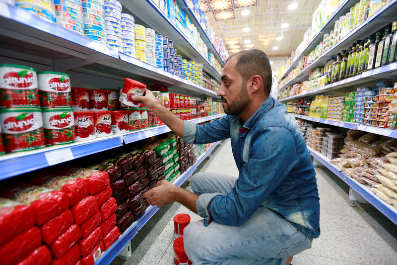 © Reuters. FILE PHOTO: A shop worker arranges the cans of Iranian tomato paste at a super market in the city of Najaf
