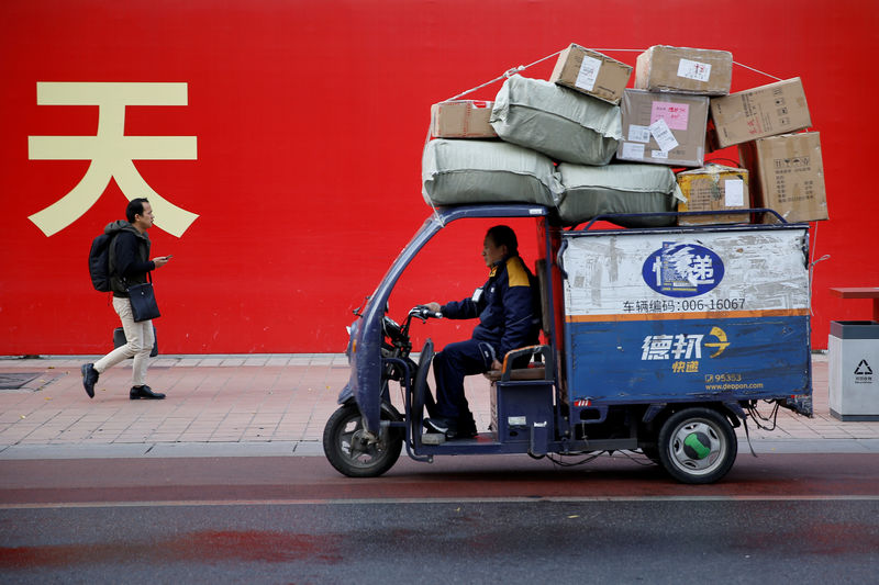 © Reuters. FILE PHOTO: An electric delivery car by Deppon Logistics drives past a banner with a government parade in Beijing