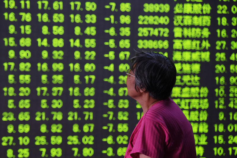 © Reuters. Woman looks at an electronic board showing stock information at a brokerage house in Hangzhou