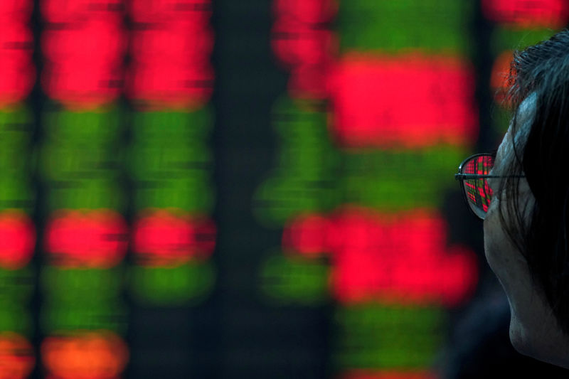 © Reuters. A man looks in front of an electronic board showing stock information at a brokerage house in Nanjing