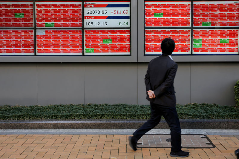 © Reuters. A man looks at an electronic board showing the Nikkei stock index outside a brokerage in Tokyo