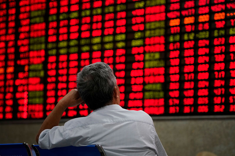 © Reuters. FILE PHOTO: An investor looks at an electronic board showing stock information at a brokerage house in Shanghai