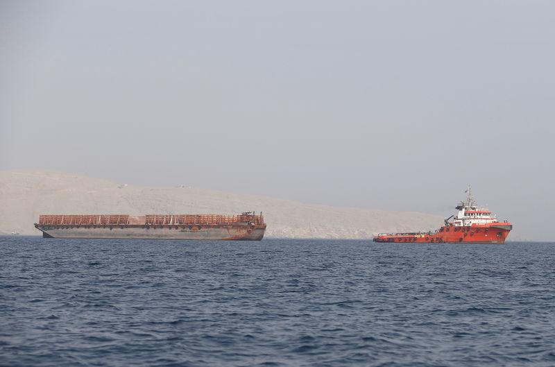 © Reuters. FILE PHOTO: A tugboat moves cargo towards the Strait of Hormuz off the coast of Musandam province, Oman