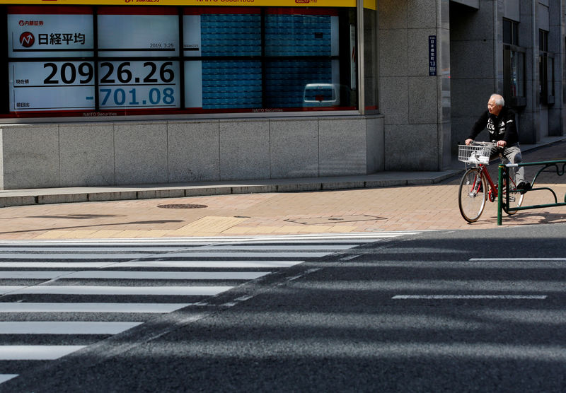 © Reuters. FILE PHOTO: A man in a bicycle stops in front of an electronic board showing the Nikkei stock index outside a brokerage in Tokyo