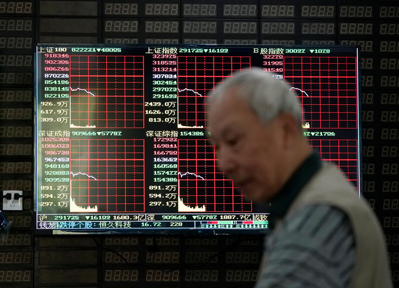 © Reuters. FILE PHOTO: An investor walks past a screen showing stock information at a brokerage house in Shanghai