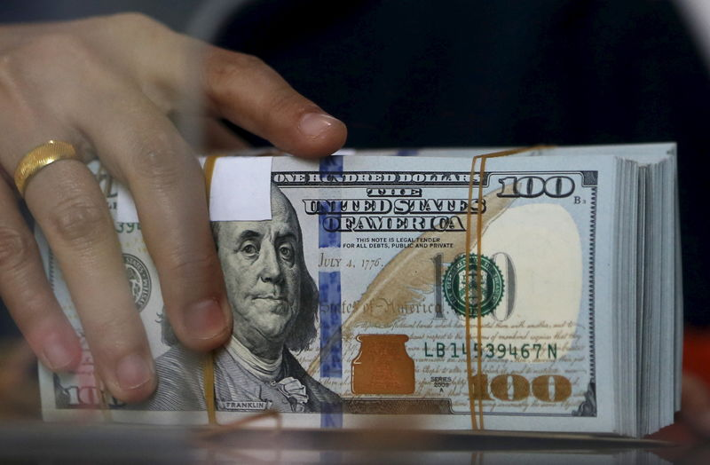 © Reuters. FILE PHOTO: An employee of a money changer holds a stack of U.S.  Dollar notes before giving it to a customer in Jakarta