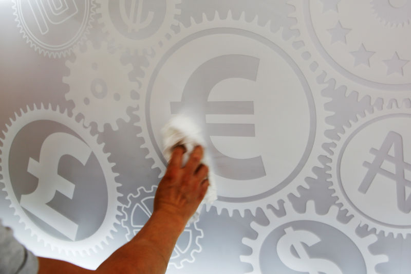 © Reuters. FILE PHOTO: A man cleans a board with different currency signs at a currency exchange office in Madrid