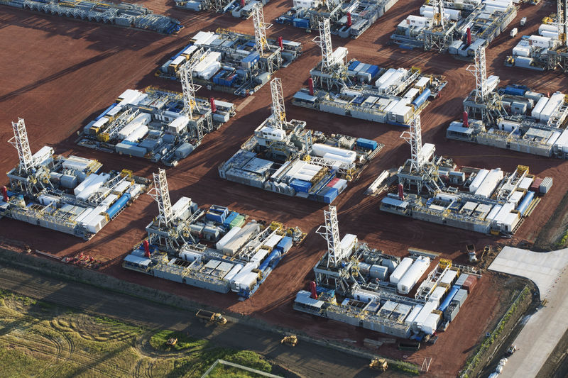 © Reuters. FILE PHOTO: Stacked rigs are seen along with other idled oil drilling equipment at a depot in Dickinson