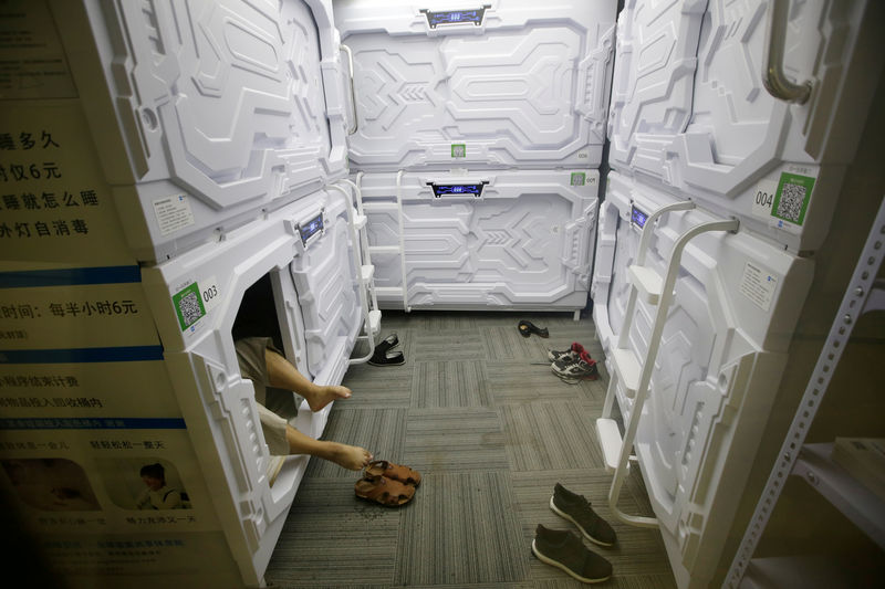 © Reuters. FILE PHOTO: An IT employee takes off shoes as he prepares to sleep in a capsule bed unit at Xiangshui Space in Beijing