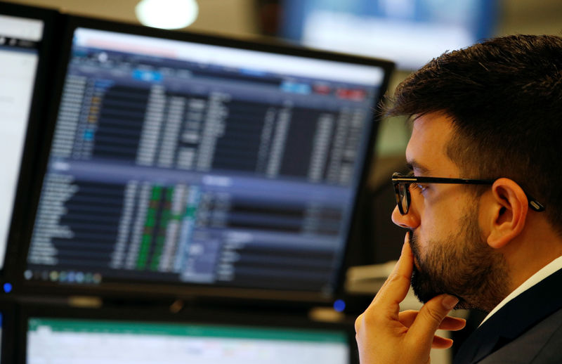 © Reuters. A trader is working on a desktop while onscreen market data on the CMC market in London