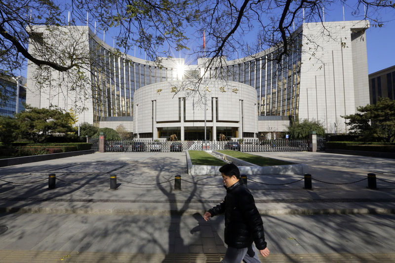 © Reuters. A man walks past the headquarters of the PBOC in Beijing