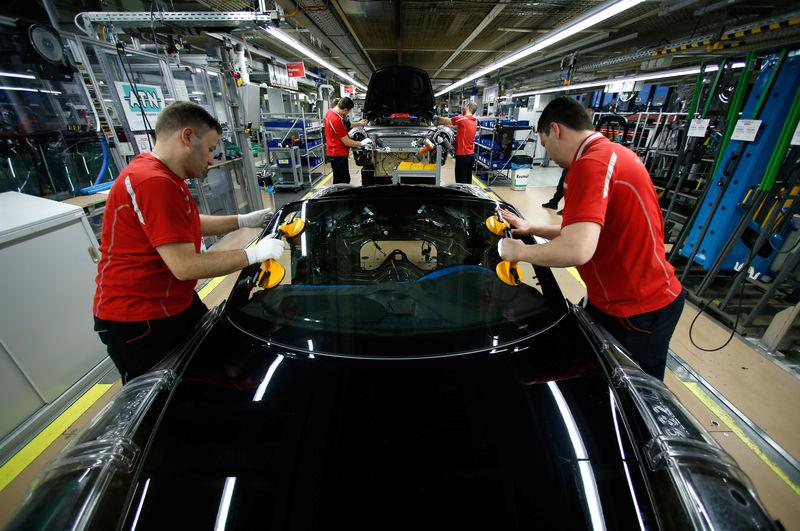 © Reuters. Employees of German car manufacturer Porsche install the windshield of a Porsche 911 at the Porsche factory in Stuttgart-Zuffenhausen