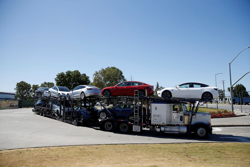 © Reuters. FILE PHOTO: A car carrier trailer carries Tesla Model 3 electric sedans, is seen outside the Tesla factory in Fremont
