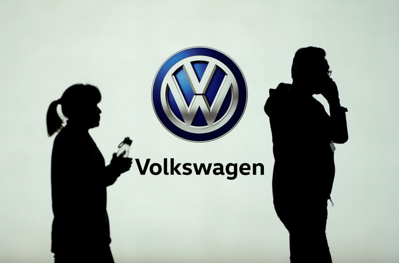 © Reuters. People pass in front of a Volkswagen logo ahead of the Shanghai Auto Show