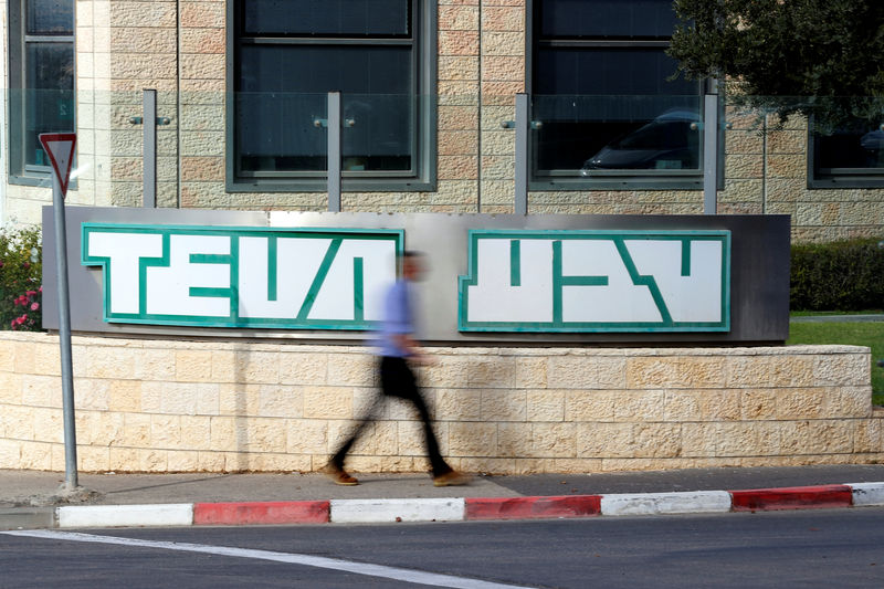 © Reuters. A man walks past the logo of Teva Pharmaceutical Industries at their plant in Jerusalem