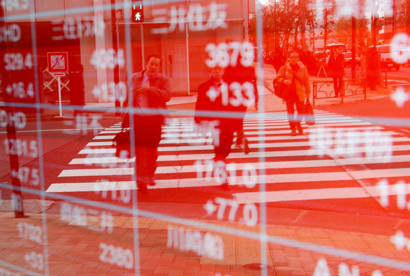 © Reuters. Pedestrians are reflected on an electronic board showing stock prices outside a brokerage in Tokyo