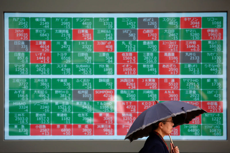 © Reuters. A passerby walks past a stock card board outside a brokerage in Tokyo