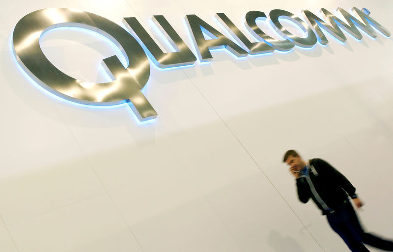 © Reuters. FILE PHOTO: A man walks past a Qualcomm advertising logo at the Mobile World Congress at Barcelona