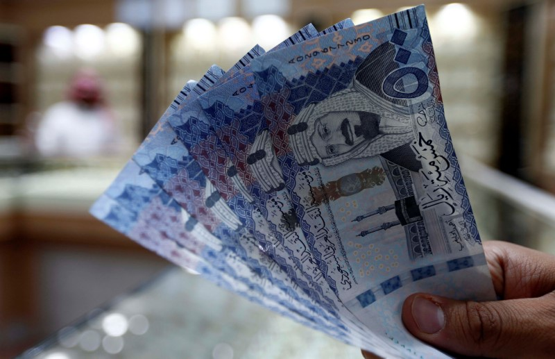 © Reuters. FILE PHOTO: Saudi money changer displays Saudi Riyal banknotes at a currency exchange shop in Riyadh