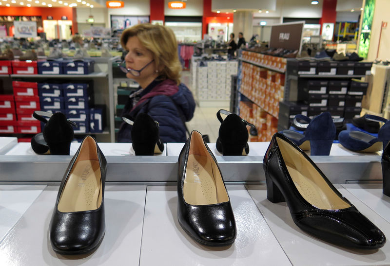 © Reuters. A woman looks for shoes in a shop in Rome
