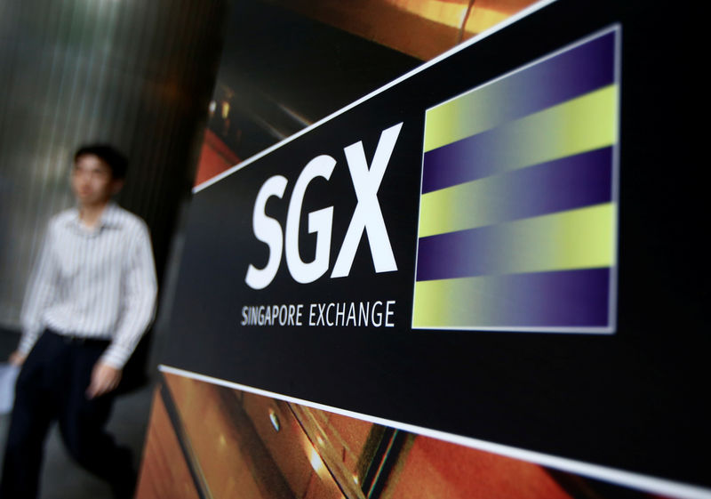 © Reuters. FILE PHOTO - An office worker walks past logo of SGX outside premises in financial district of Singapore