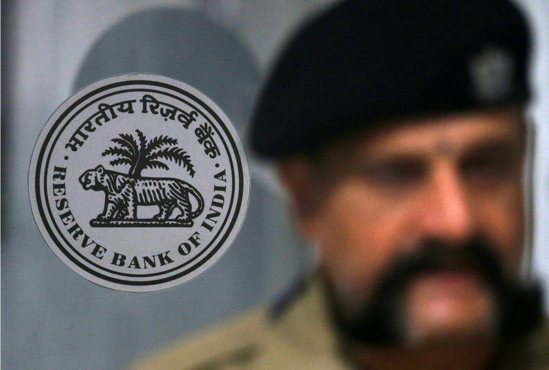 © Reuters. A security guard stands next to the logo of Reserve Bank of India inside its headquarters in Mumbai