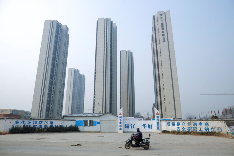 © Reuters. A man rides a scooter past apartment highrises that are under construction near the new stadium in Zhengzhou