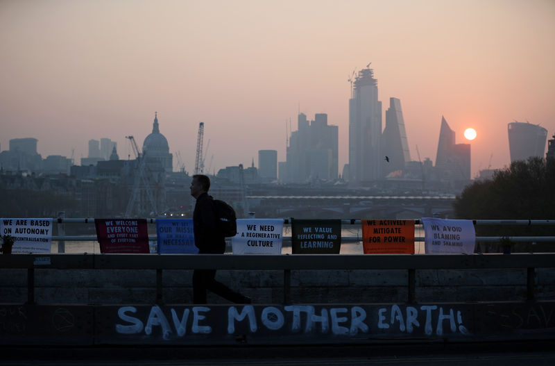 © Reuters. FILE PHOTO: A commuter walks along Waterloo Bridge, which is being blocked by climate change activists, during the Extinction Rebellion protest in London